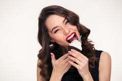 Beautiful curly young woman biting birthday cupcake with candle Stock Photos