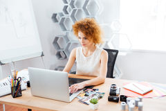 Beautiful curly young woman photographer using laptop with graphic tablet Royalty Free Stock Image