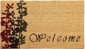Beautiful cursive welcome peach color doormat with red and black flower plant. Isolated on a White Background royalty free stock images