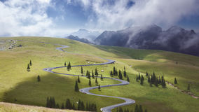 Beautiful curved road towards the mountain peaks. Winding asphalt road at fresh morning through spruce trees on idyllic green fields stock images