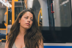 Beautiful curvy girl posing in a metro car. Beautiful young curvy girl in tank top posing in a metro car Royalty Free Stock Images
