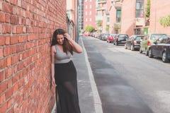 Beautiful curvy girl posing in an urban context. Beautiful young curvy girl in tank top posing in an urban context Stock Images