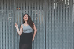 Beautiful curvy girl smoking a cigarette in an urban context Stock Photos