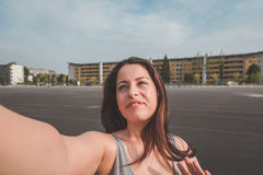Beautiful curvy girl taking a selfie. Beautiful young curvy girl in tank top taking a selfie in an urban context Stock Photography