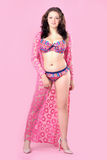 Beautiful curvy young woman wearing colorful bikini with gown on pink background. Stock Photos