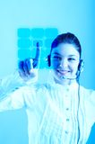 Beautiful Customer Representative. With headset smiling during a telephone conversation entering a code on a virtual keyboard Royalty Free Stock Photography