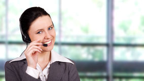 Beautiful customer representative. With headset smiling during a telephone conversation royalty free stock photo