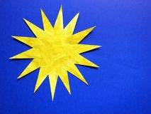 Cut and painted yellow sun  on blue background Royalty Free Stock Photos