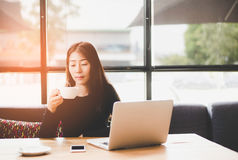 Beautiful cute asia girl in the cafe near the window with coffee smiling and work space, relax. Royalty Free Stock Image
