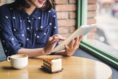 Beautiful cute asian young businesswoman in the cafe, using digital tablet and drinking coffee smiling stock photography