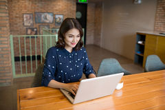 Beautiful cute asian young businesswoman in the cafe, using lapt Stock Image