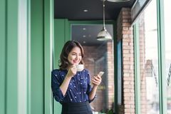 Beautiful cute asian young businesswoman in the cafe, using mobi Stock Images
