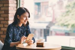 Beautiful cute asian young businesswoman in the cafe, using mobile phone and drinking coffee smiling stock photography