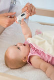 Beautiful cute baby girl with doctor taking temperature Stock Photos
