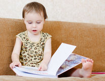 Beautiful cute baby reading a book Stock Images