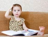 Beautiful cute baby reading a book Royalty Free Stock Photography