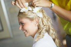 Beautiful, cute blond bride doing hair with flowers before weddi. Ng day. Long lashes, white flowers, smilling and happy. Perfect wedding preparation Royalty Free Stock Photo