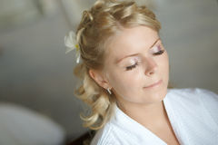 Beautiful, cute blond bride doing makeup before wedding day. Lon. G lashes, white flowers in hair, smilling and happy. Perfect wedding preparation Royalty Free Stock Images
