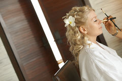 Beautiful, cute blond bride doing makeup before wedding day. Lon. G lashes, white flowers in hair, smilling and happy. Perfect wedding preparation Stock Photos
