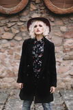 Beautiful cute  blonde girl with curly hair in a hat and black coat near a stone wall Stock Photos