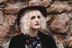 Beautiful cute  blonde girl with curly hair in a hat and black coat near a stone wall Stock Image
