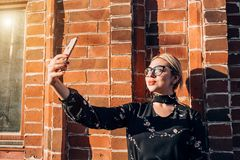 Beautiful cute blonde model in dress posing in the city stock photo