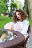 Beautiful cute cheerful girl in a bright dress with curly hair and bright make-up sitting at an outdoor cafe and waiting for royalty free stock photography