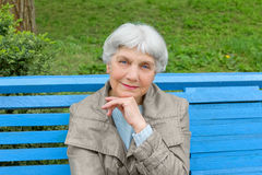 beautiful cute elderly woman sitting in park bench blue Royalty Free Stock Images