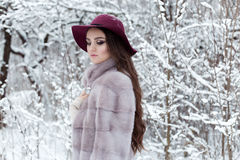 Beautiful cute elegant girl in a fur coat and hat walking in the winter forest bright frosty morning Royalty Free Stock Photography