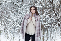 Beautiful cute elegant girl in a fur coat walks in the winter forest bright frosty morning Royalty Free Stock Images