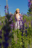 Beautiful cute gentle girl in white sundress with a wreath of roses on her head walks a field with lupine Royalty Free Stock Image