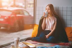Beautiful cute girl in the cafe sitting on her knees near the window with a cup of coffee and looking on the street. She Royalty Free Stock Images