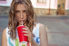 Beautiful cute girl with curly hair in sunglasses with a paper glass and a straw drinking a drink in the city on a sunny summer ev Royalty Free Stock Image
