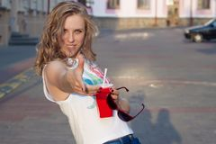 Beautiful cute girl with curly hair in sunglasses with a paper glass and a straw drinking a drink in the city on a sunny summer ev Royalty Free Stock Photo