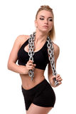 Beautiful and cute girl with metal chain posing in the studio. Woman bodybuilder or fitness trainer in his underwear Stock Photography