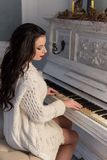 Beautiful cute girl in white warm jacket at home playing on old piano Royalty Free Stock Photos