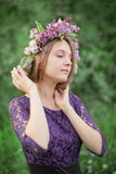 Beautiful cute girl in a wreath of lilacs Stock Images