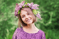 Beautiful cute girl in a wreath of lilacs Royalty Free Stock Photography