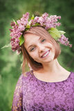 Beautiful cute girl in a wreath of lilacs Royalty Free Stock Images
