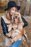 Beautiful cute happy girl in a black hat playing with her dog Royalty Free Stock Images