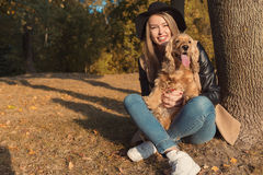 Beautiful cute happy girl in a black hat playing with her dog in a park in autumn another sunny day Royalty Free Stock Photos