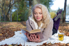 Beautiful cute happy smiling girl lying on the ground and reads a book in autumn Park the Park with a mug of hot tea Royalty Free Stock Image
