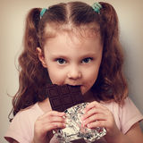 Beautiful cute kid girl eating dark healthy chocolate with fun l Stock Images
