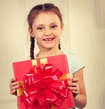 Beautiful cute kid girl holding present box with red ribbon bow Royalty Free Stock Image