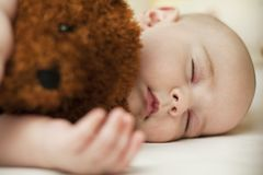 Cute little baby sleeping in a sweet sleep hugging a bear royalty free stock photography