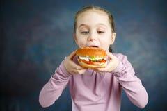 Beautiful Cute Little Caucasian Blond Girl With Hamburger royalty free stock image