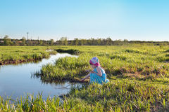 Beautiful cute little girl in blue dress sitting by creek Stock Photo