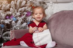 A beautiful cute little girl dressed in an elegant evening red dress sits on the couch and opens a New Year`s gift. stock photo