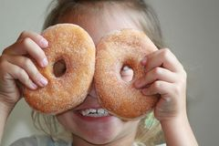 Playing with Food. Beautiful, cute, little girl holding two donuts in front of her eyes. Looking through the holes with a big smile on her face Royalty Free Stock Photo