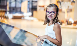 Beautiful cute little girl studying orientation plan in shopping mall. Shopping Center Store Guide. Modern touch screen technology Stock Images